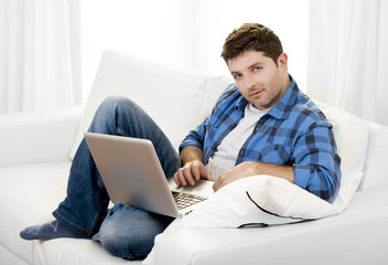 Attractive man with computer sitting on couch