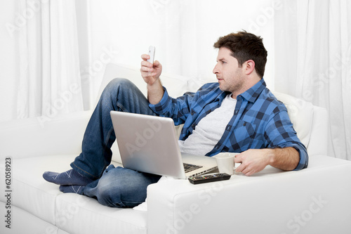relaxed man with computer writting text on mobile
