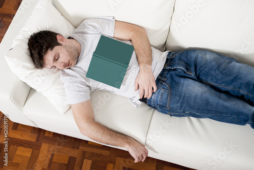 tired young man sleeping on couch with book on lap