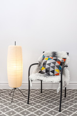 Chair with bright cushion and elegant floor lamp