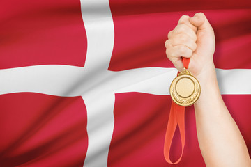 Medal in hand with flag on background - Kingdom of Denmark