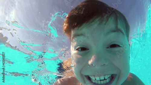 Cute teen boy dives in blue pool with open eyes