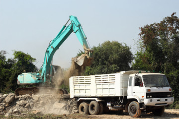 excavator loading stone dump truck on construction site