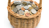 Wicker basket with coins of different countries