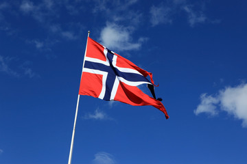 A Norwegian flag blowing in the wind against blue sky with cloud