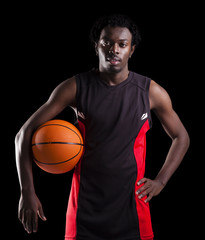 Portrait of a basketball player holding a ball against dark back
