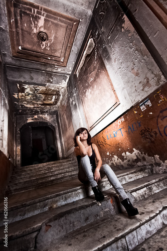 Beautiful young girl sitting on stairs at old abandoned building