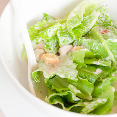Fresh salad in a white bowl close up