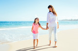 Happy mother and young daughter walking on the beach