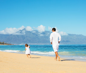 Father and daughter walking together at the beach