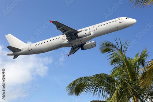 canvas print picture Flugzeug startet zwischen Palmen in den Urlaub