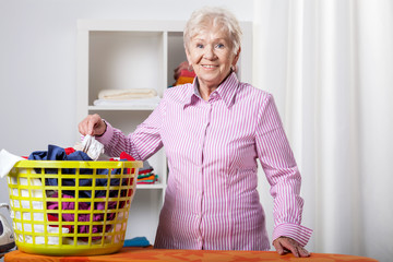 Senior lady during folding laundry