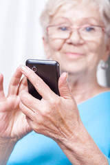 Senior lady using cellular phone application