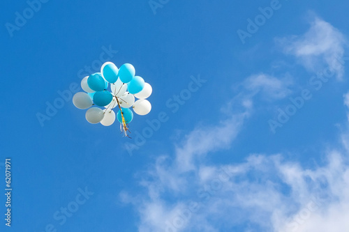 a bunch of blue and white balloons in the sky