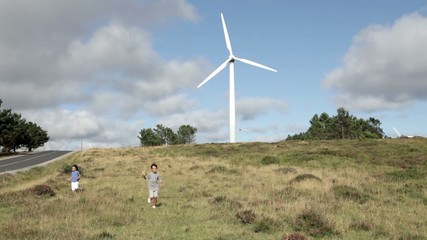 Niños corriendo entre molinos de viento