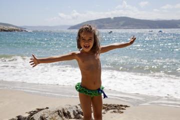 Niña con los brazos abiertos y alegre en la playa