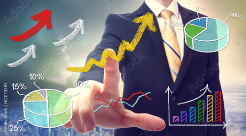 Businessman pointing at rising arrows