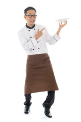 Asian male chef pointing an empty plate