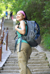 woman hiker climbing steep stone stairs on mountain huashan peak