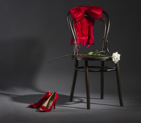 Sexy lingerie, shoes and a white rose on a retro chair.