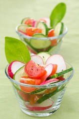 fresh vegetable salad in a glass beaker, vertical, close-up