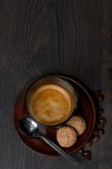 glass of espresso, almond cookies on dark background, top view