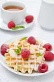 waffles with fresh raspberries and nuts on a plate for breakfast