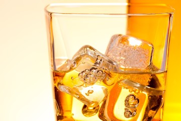 detail of a glass of drink like whisky with ice