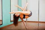 Happy pole dancer trying a routine