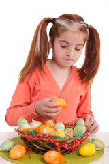 beautiful little girl decorate the basket with Easter eggs