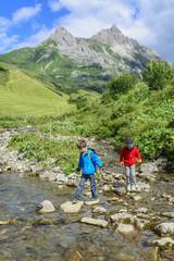 Zwei Jungs überqueren einen Bergbach