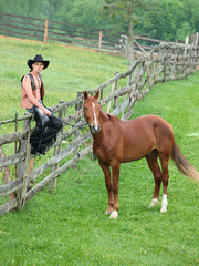 Cowboy with horse on paddock