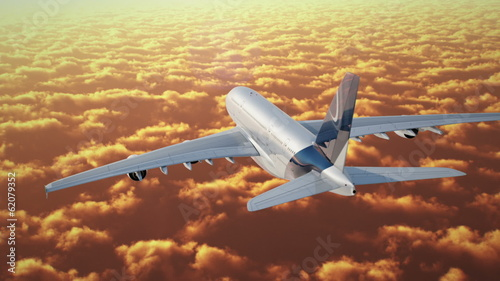 Jet flying over cloudscape at sunset