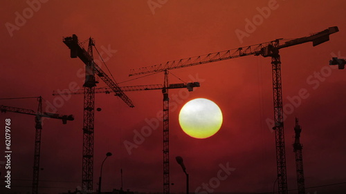 construction cranes working on background of setting sun - timel