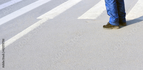 legs of a man at a crosswalk