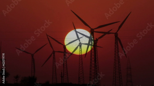 wind farm - turning windmills on background of setting sun timel