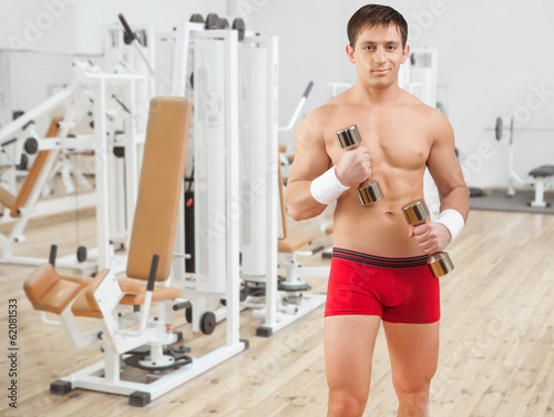 beautiful shirtless sportsman holding small dumbbells
