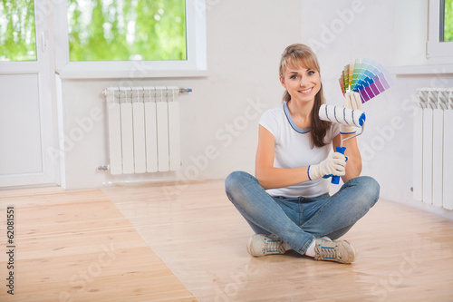 beautiful smiling female worker sitting on wooden floor and show