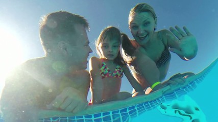 Happy family having fun in their family swimming pool
