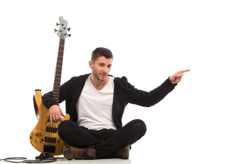 Male guitarist sitting on the floor and pointing