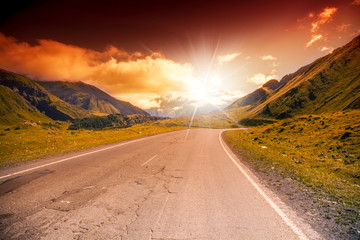 road in the mountains landscape with bright sunset sky