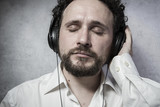 Trendy, listening and enjoying music with headphones, man in whi