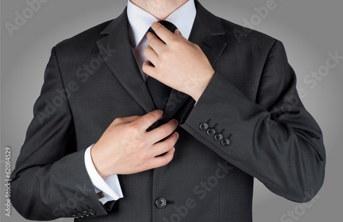 businessman in black costume tie one's necktie