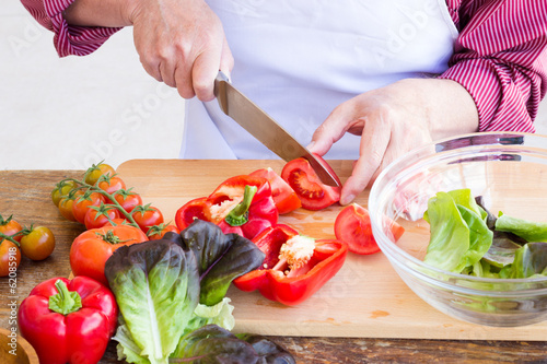 Man cutting vegetables for healthy salad