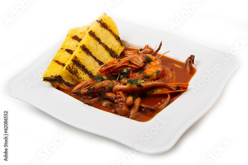 fish soup with grilled polenta on white dish