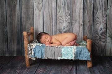 Newborn Baby Boy Sleeping on a Tiny Bed