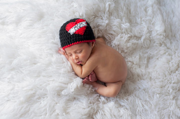 "Newborn Baby Boy Wearing a ""Love Mom"" Hat"
