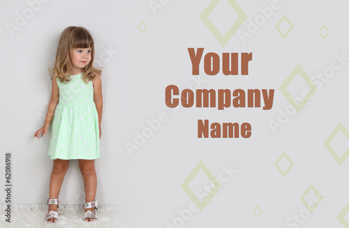 Little cute girl on carpet, on gray background