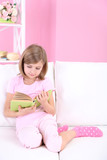 Little girl reading book sitting on sofa in room