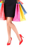 Female in red shoes holding shopping bags isolated on white